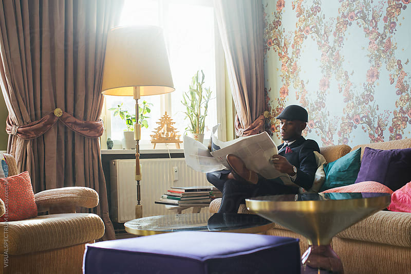 Elegant Young Black Man Reading Newspaper in Stylish Living Room by Julien L. Balmer for Stocksy United