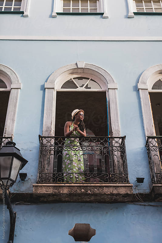 Brazil. Woman looking out from the terrace by Mauro Grigollo for Stocksy United