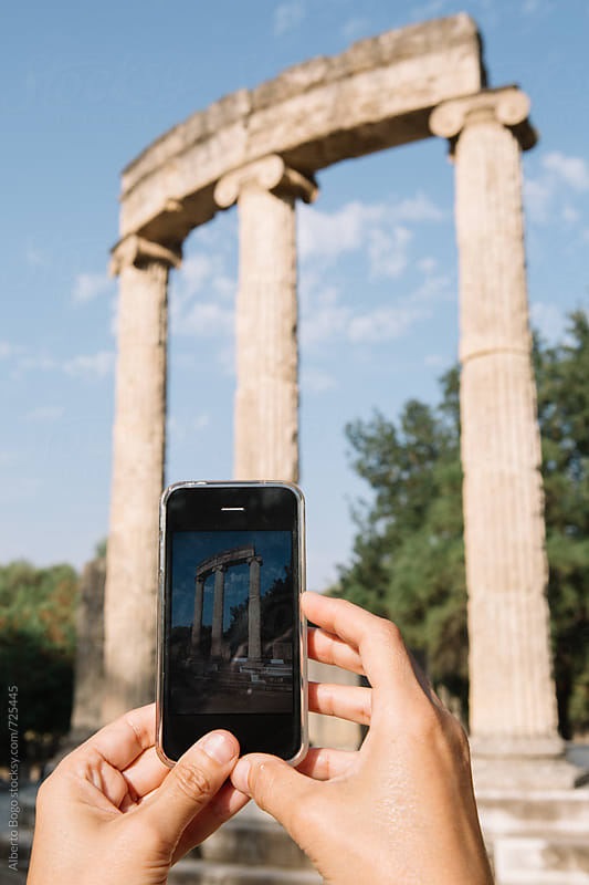 Woman taking a photo up in the greek temple by Alberto Bogo for Stocksy United