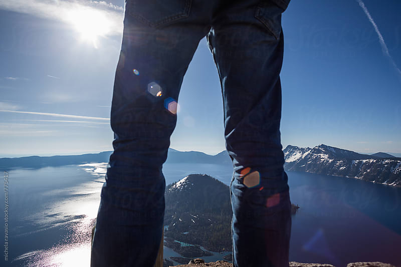 Man standing in front a crater lake, Oregon by michela ravasio for Stocksy United