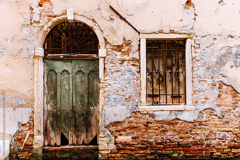 A doorway and window in a decaying wall in Venice, Italy by Gary Radler Photography for Stocksy United
