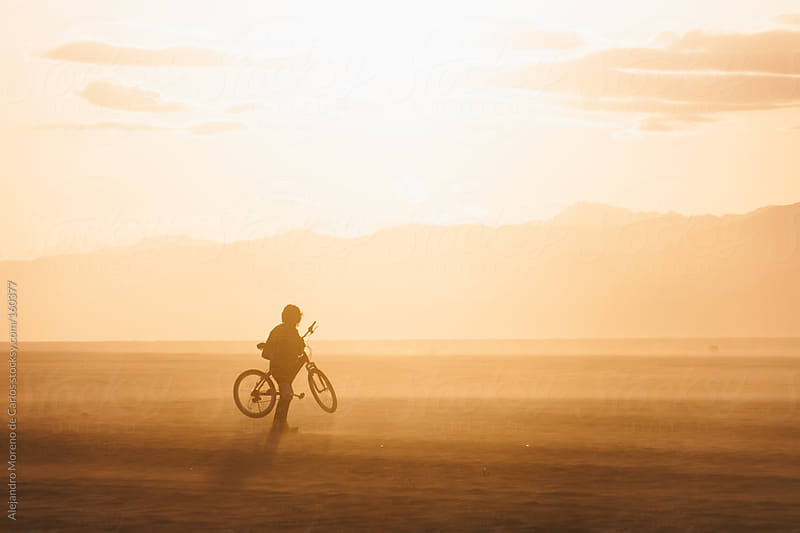 Silhouette of young man holding a bike on a beach at sunset in summer by Alejandro Moreno de Carlos for Stocksy United
