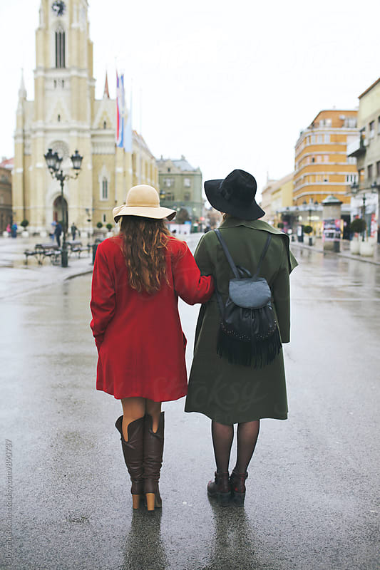 Two fashionable female friends walking on street by Jovana Rikalo for Stocksy United