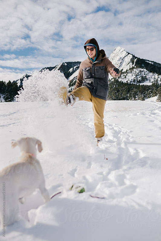 Man playing with his puppy in the snow by Kristine Weilert for Stocksy United