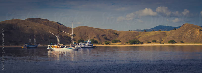 Sail boats moored up in a bay on a barren islands near Komodo by Soren Egeberg for Stocksy United