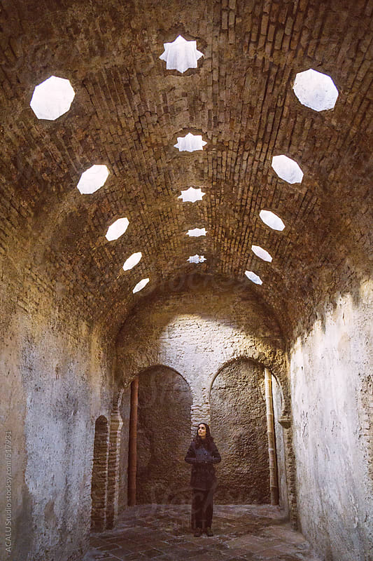 Woman inside abandoned Arab baths by ACALU Studio for Stocksy United