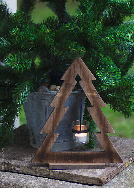 Christmas tree shaped wooden candle holder close to spruce tree in garden by Laura Stolfi for Stocksy United