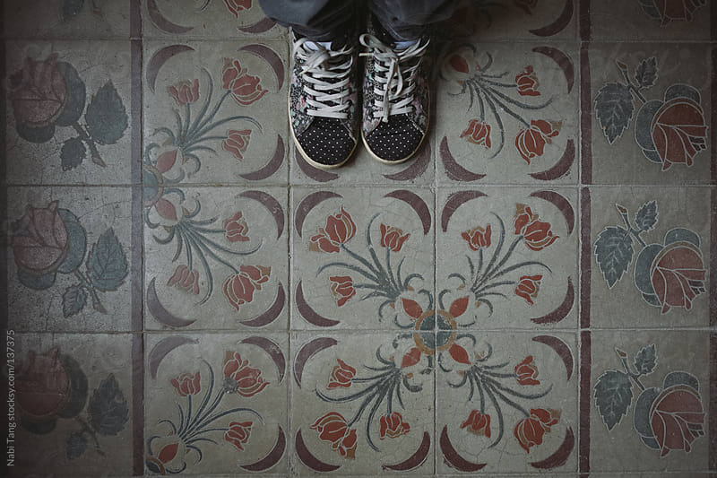 Canvas shoes on vintage tiles by Nabi Tang for Stocksy United
