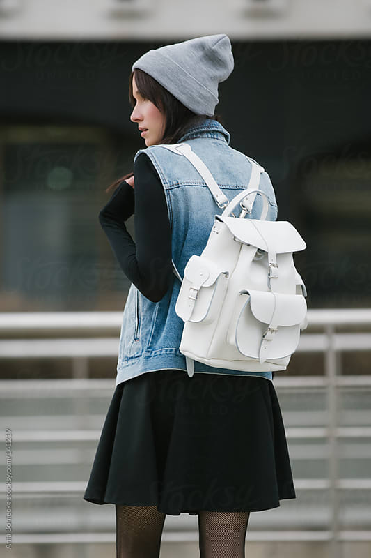 A student wearing a white leather backpack facing away by Ania Boniecka for Stocksy United