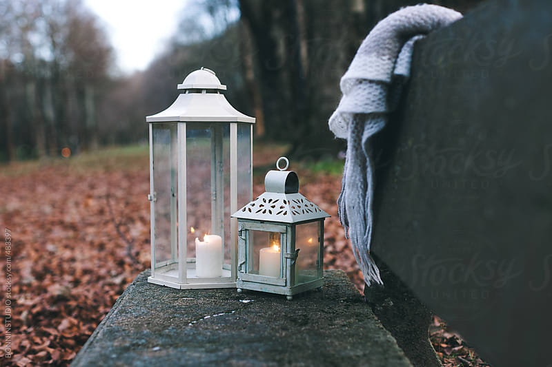 Still life of two candle holders and a white blanket on a bench. by BONNINSTUDIO for Stocksy United
