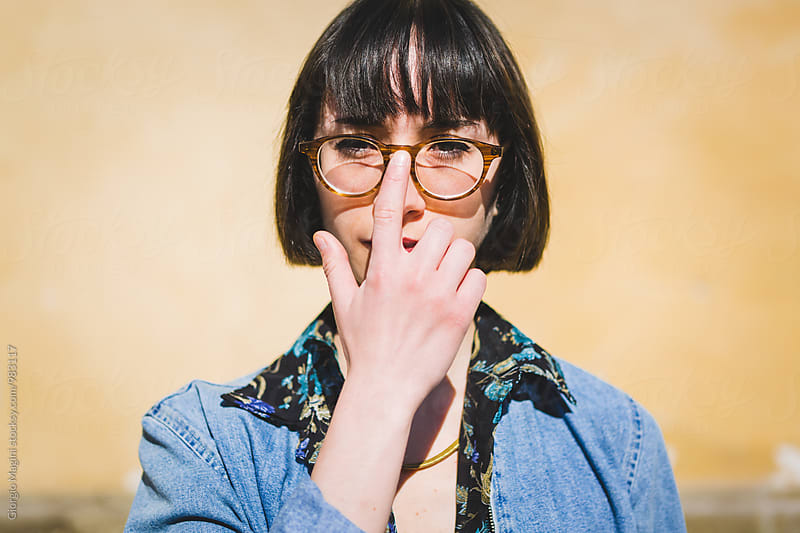 Nerdy Young Woman Fixing her Glasses by Giorgio Magini for Stocksy United