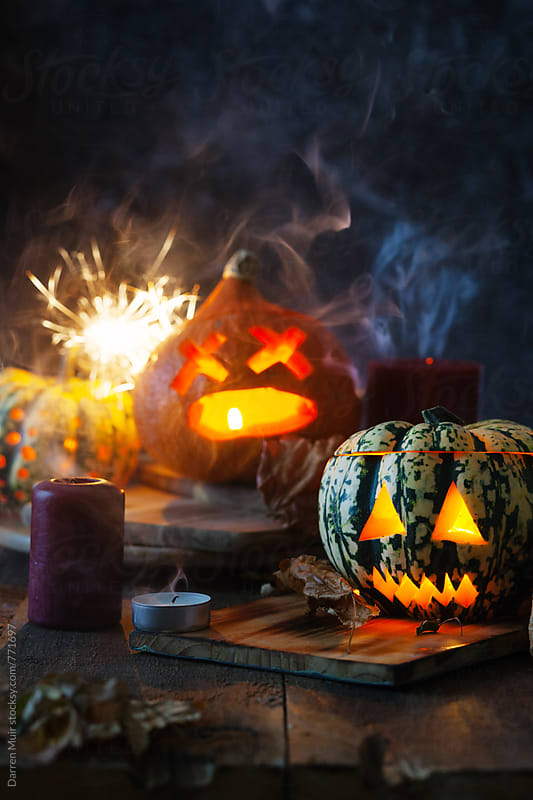 Halloween pumpkins with fireworks and smoke. by Darren Muir for Stocksy United