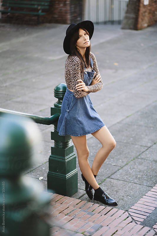A woman leaning against a pole wearing a denim dress and a wide brimmed hat by Ania Boniecka for Stocksy United