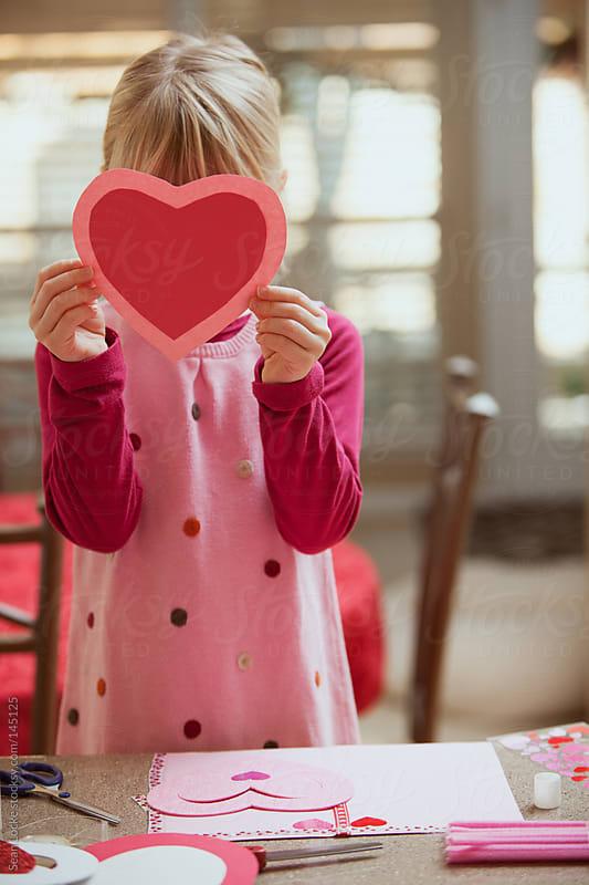 Valentine: Girl Hiding Behind Paper Heart by Sean Locke for Stocksy United