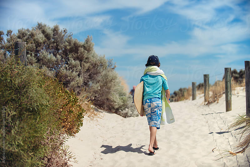 Boy walking through sand dunes to the beach by Angela Lumsden for Stocksy United