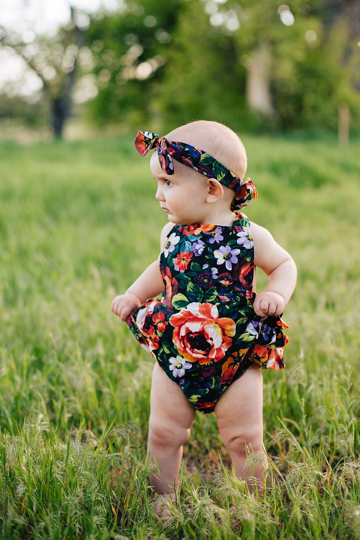 1fdfa8d094bb Cute one-year old girl in floral romper and headband outside in tall grass.
