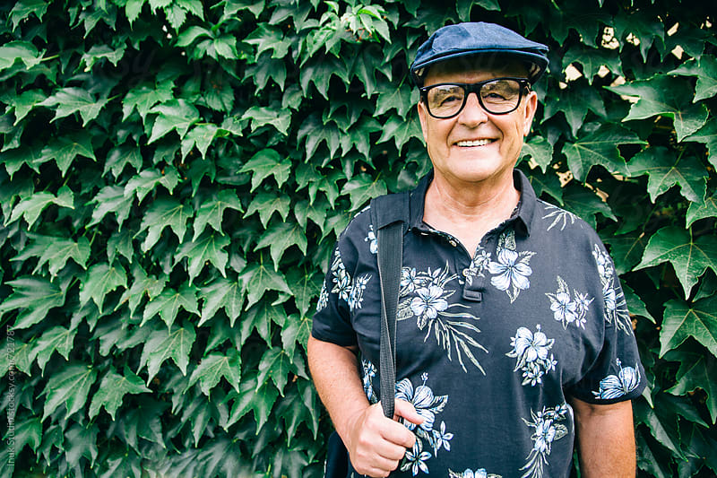 Stylish senior man portrait wearing glasses , a beret and flower polo shirt on ivy background by Inuk Studio for Stocksy United