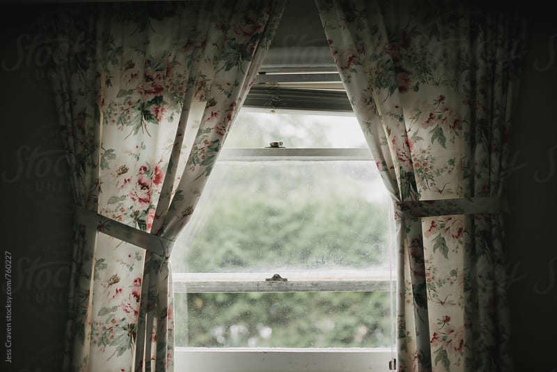 Dark shadowy room looking outside window with vintage floral curtains by Daring Wanderer for Stocksy United