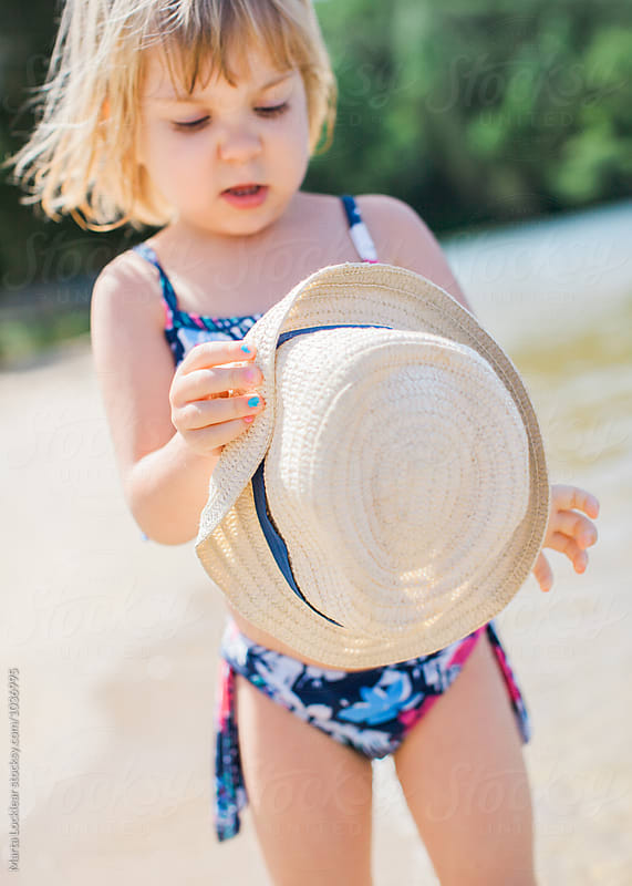 Little girl and a beach hat by Marta Locklear for Stocksy United
