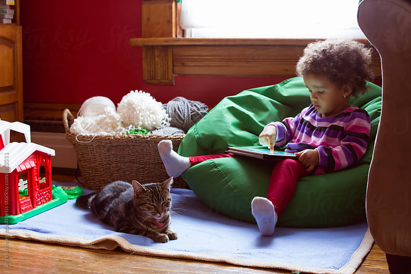 Young toddler girl sitting in a bean bag chair plays with an electronic tablet by anya brewley schultheiss for Stocksy United