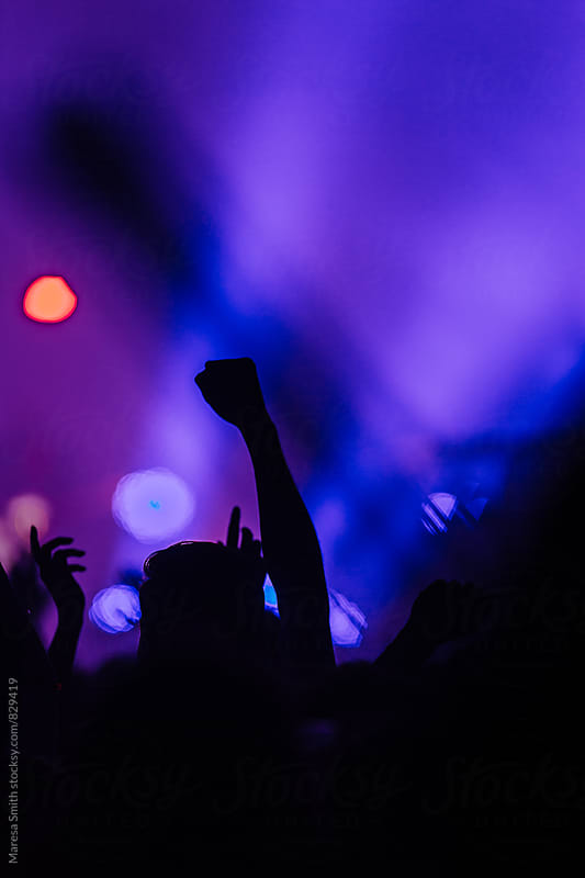 Silhouetted fist in the air at a colourful concert by Maresa Smith for Stocksy United