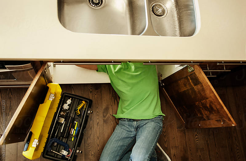 Handyman working under the kitchen sink by W2 Photography for Stocksy United