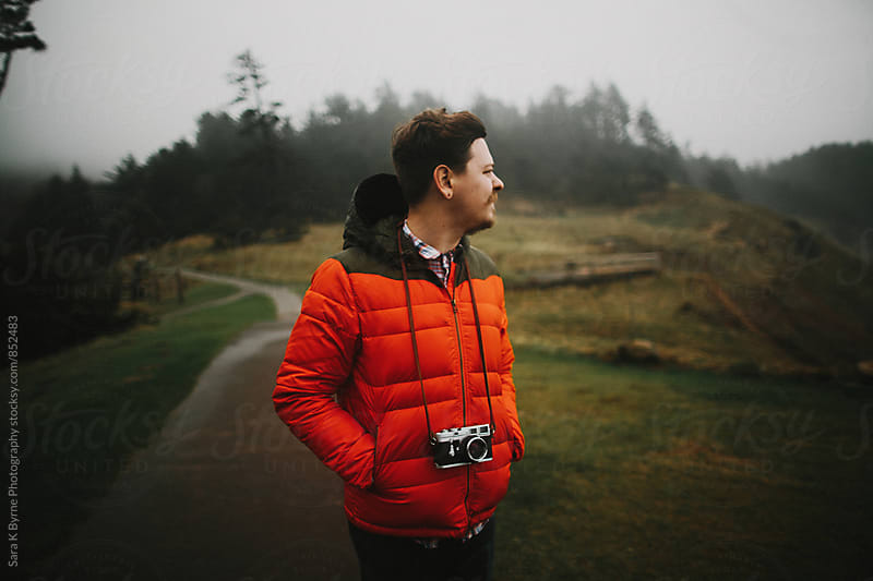 guy wearing orange coat and camera by Sara K Byrne Photography for Stocksy United