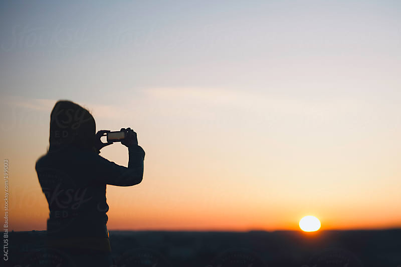 Woman taking a sunset picture with a mobile phone. by CACTUS Blai Baules for Stocksy United