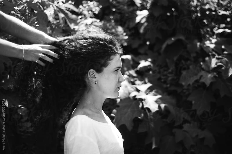A black and white film portrait of a young beautiful woman with hands in the hair by Anna Malgina for Stocksy United