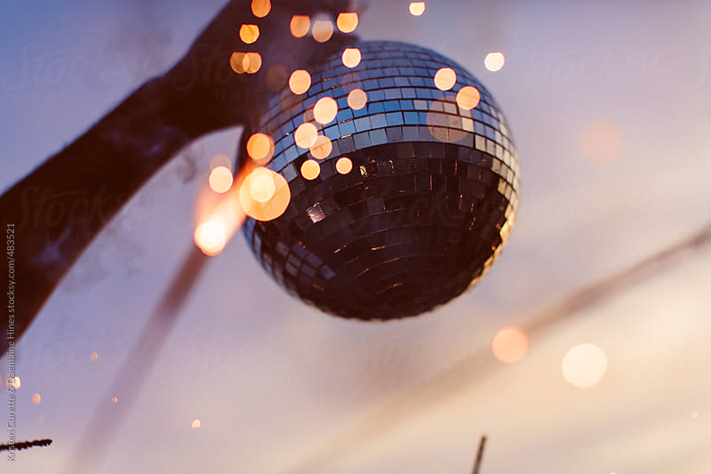 A person holding up a disco ball at the beach by Kristen Curette Hines for Stocksy United
