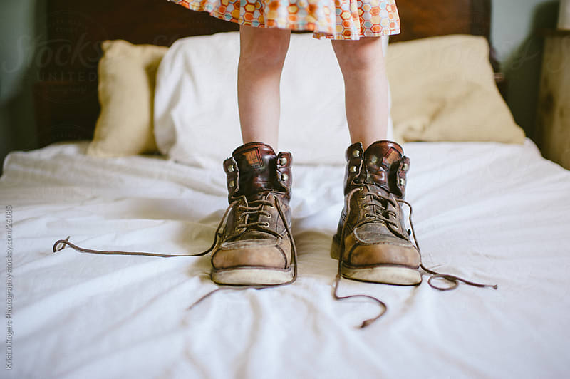 Little girl standing on bed in her daddy's boots by Kristin Rogers Photography for Stocksy United