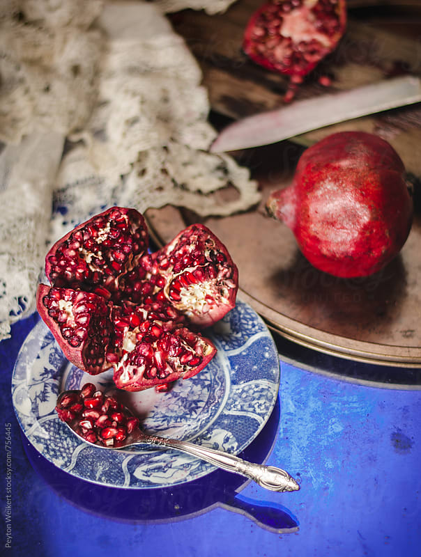 Sliced Pomegranate on Blue Vintage Plate on top of Blue Glass beside Lace Napkin by Peyton Weikert for Stocksy United