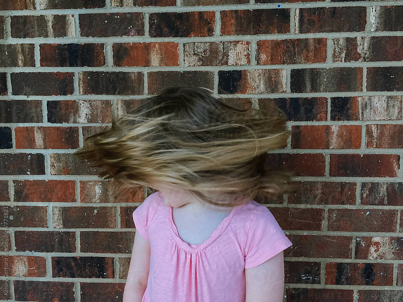 A young girl shakes her hair back and forth after a haircut. by Kelsey Gerhard for Stocksy United