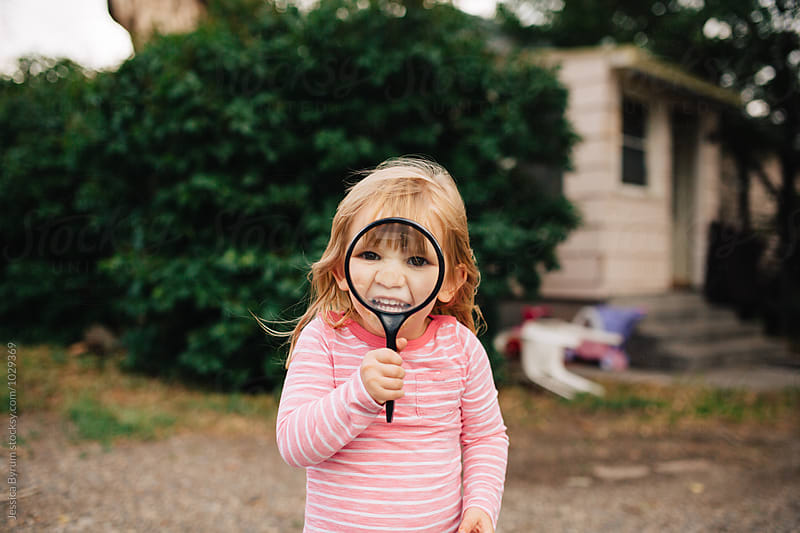 Toddler girl playing with a large magnifying glass in her backyard. by Jessica Byrum for Stocksy United