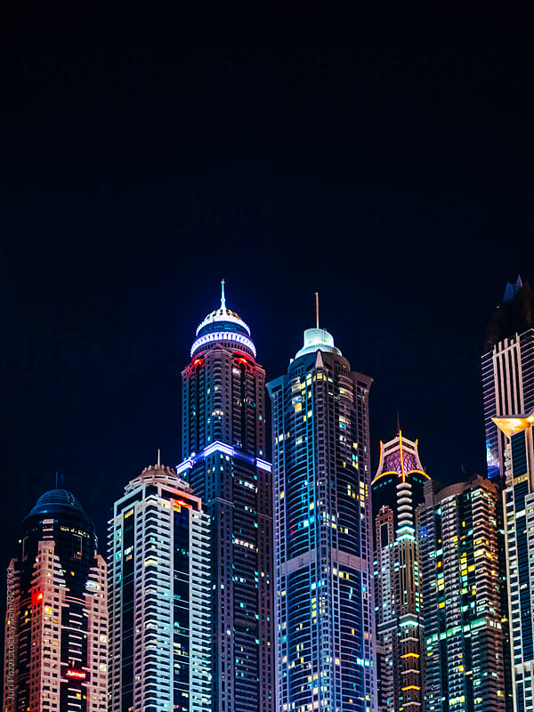 Dubai Marina skyscrapers at night by Juri Pozzi for Stocksy United