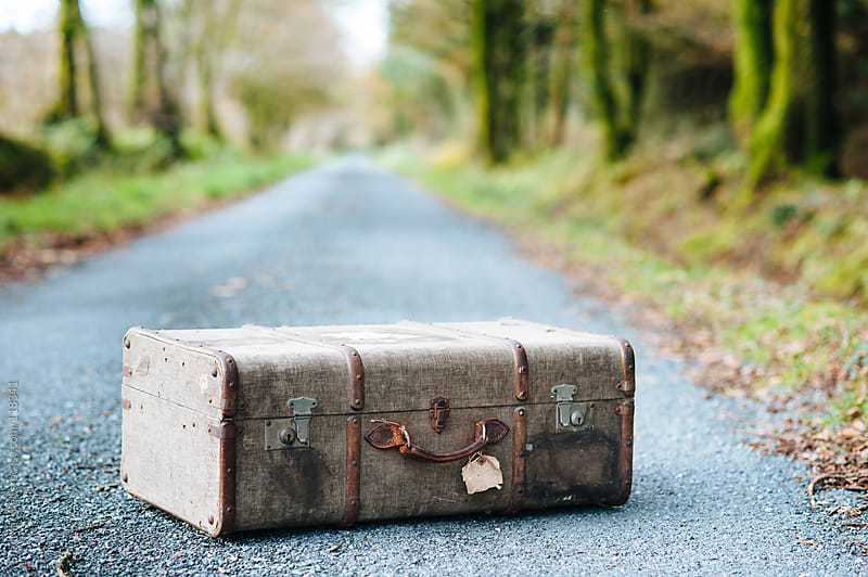 Vintage suitcase on a country road in autumn by Suzi Marshall for Stocksy United