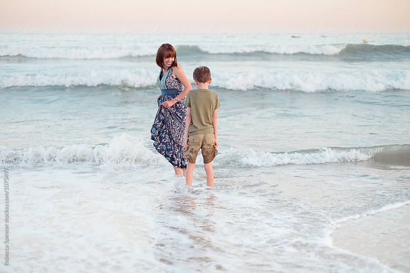 Mother and child standing in the sea letting their clothes get wet by Rebecca Spencer for Stocksy United