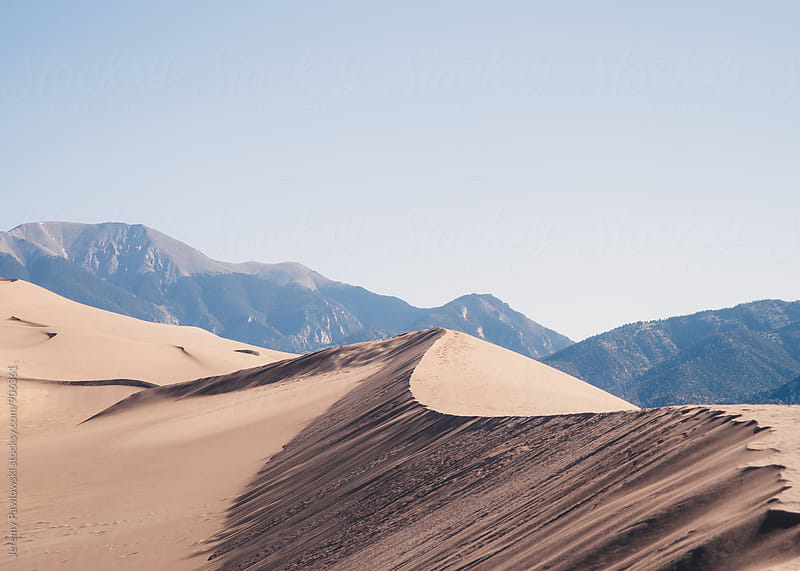 Ridges in sand dune with mountains in background by Jeremy Pawlowski for Stocksy United