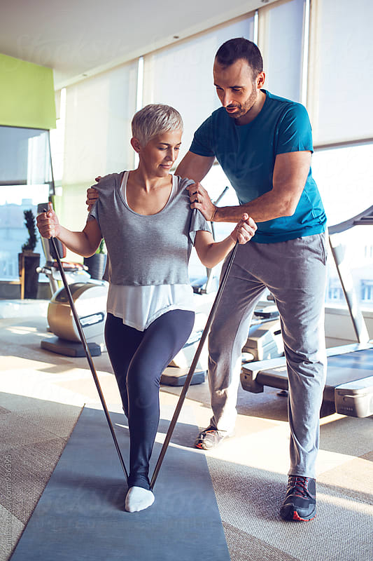 Woman Doing Exercise  with her Fitness Instructor in the Gym by Lumina for Stocksy United