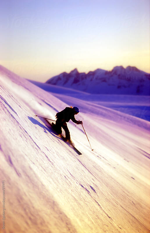 Young adult female skier skiing a steep snow slope at sunset by Soren Egeberg for Stocksy United