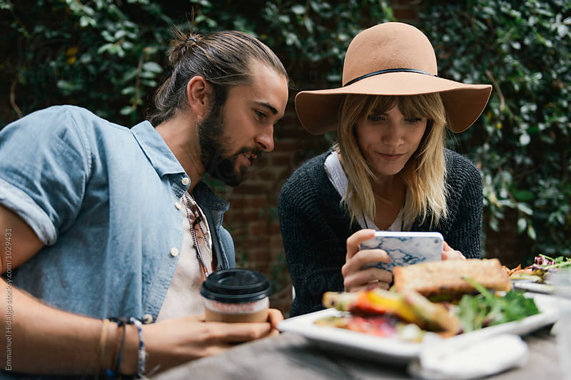 Man watches while his girlfriend takes a photo of her food with a smart phone by Emmanuel Hidalgo for Stocksy United