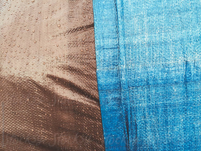 Close up of brown and blue industrial tarpaulin covering commercial fishing equipment by Paul Edmondson for Stocksy United