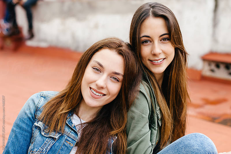Two young female sitting in outdoors.  by BONNINSTUDIO for Stocksy United