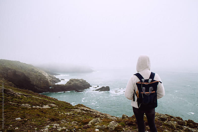 PERSON STANDING ON A MISTY CLIFF. by Helen Rushbrook for Stocksy United