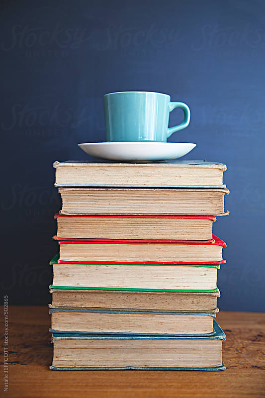 a pile of old books to read with coffee cup sitting on top by Natalie JEFFCOTT for Stocksy United