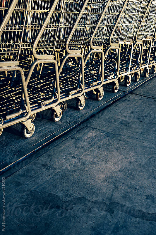 Metal grocery carts lined up on sidewalk outside supermarket by Paul Edmondson for Stocksy United