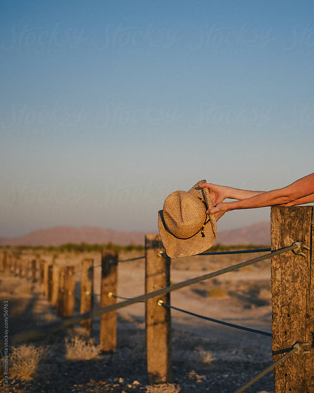 fence into the distance with cowboy hat in foreground by Tara Romasanta for Stocksy United