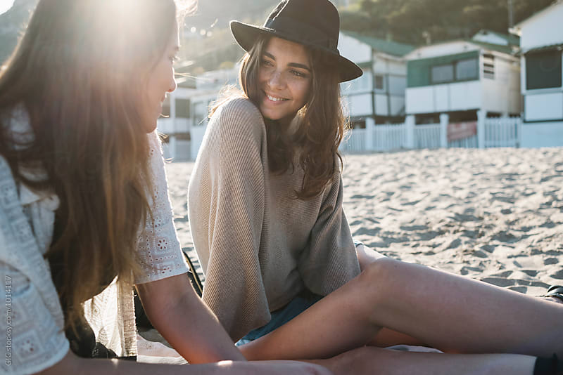 Young women relaxing at the beach at sunset by WAVE for Stocksy United
