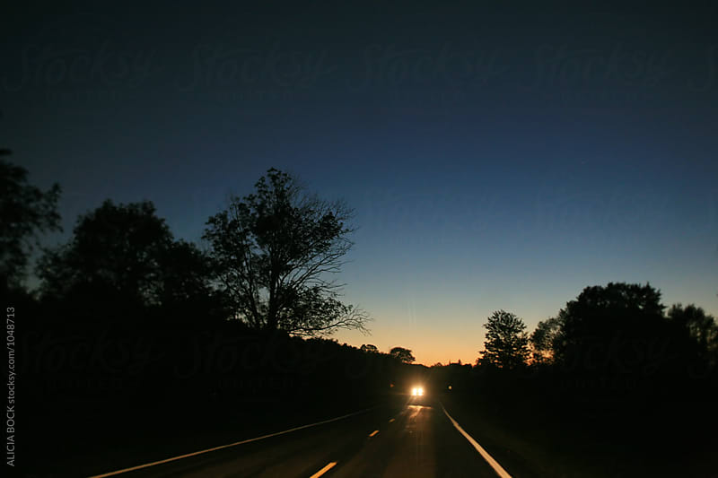 A Dark Road With One Car On A Summer Night by ALICIA BOCK for Stocksy United