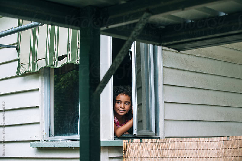 Little girl at window looking out. by Shannon Aston for Stocksy United